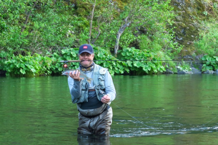 trout in hand rod in mouth